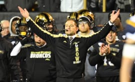 P.J. Fleck extends his arms, asking for the blessings of DJ Khaled.