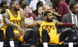 LeBron James and Kyrie Irving sit on the bench during a 2017 game.