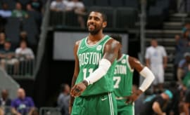 Kyrie Irving smiles on the court for the Celtics.