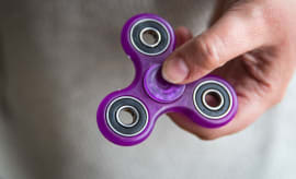 a woman holds a fidget spinner