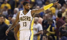Paul George points during game.
