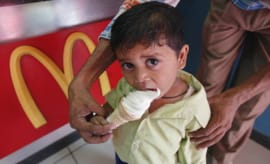 A Child eating ice cream at a McDonalds outlet, India.