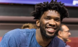 Joel Embiid laughs during a press conference.