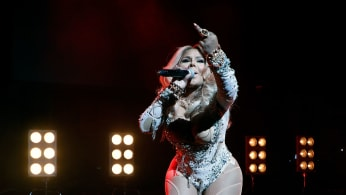 This is a photo of Lil Kim performing with her middle finger up.