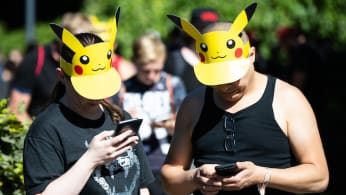 Two participants with Pokemon sun vizors playing 'Pokemon Go' on their mobile phones.