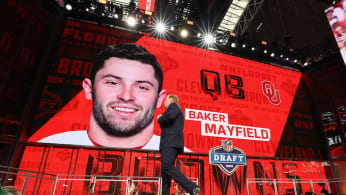 Roger Goodell walks past a video board displaying an image of Baker Mayfield.