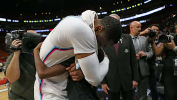 Dwyane Wade hugs his son, Zion, after a 91-85 win against the Milwaukee Bucks.
