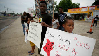 Demonstrators protest the fatal police shooting of Alton Sterling