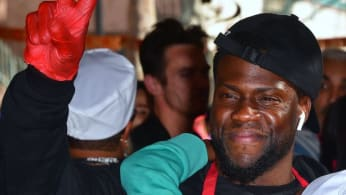 Kevin Hart gestures between serving volunteers who will serve the homeless.