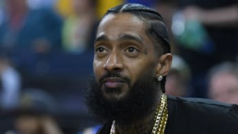 Rapper Nipsey Hussle sitting at courtside looks on during an NBA basketball game