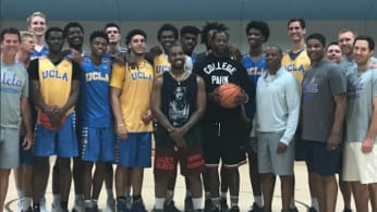 Kanye West and 2 Chainz pose for a photo with the UCLA Bruins basketball team.