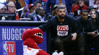 Toronto Raptors mascot, The Raptor, gets a pat on the head from singer Drake