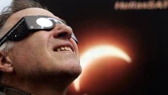 A man watches a solar eclipse.