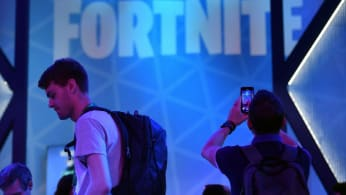"A visitor takes pictures at the stand of the ""Fortnite"" computer game"