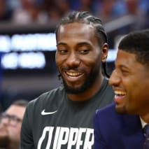 Kawhi Leonard and Paul George smile while sitting on the bench during their game.