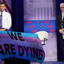 Pete Buttigieg and Anderson Cooper react as protestors display banners.