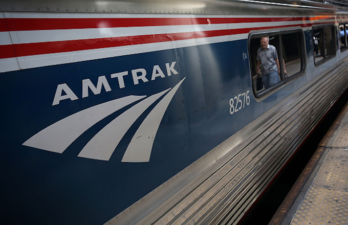 A passenger passes by an Amtrak train
