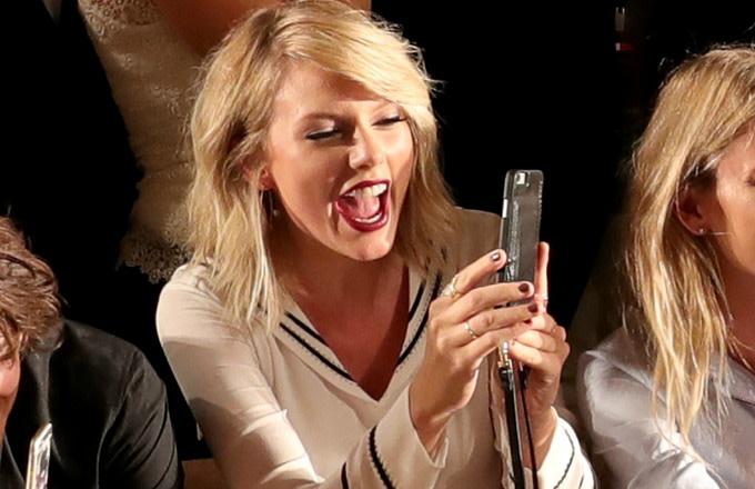 Taylor Swift checks her phone.