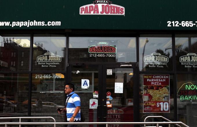 A man walks by a Papa Johns pizza restaurant