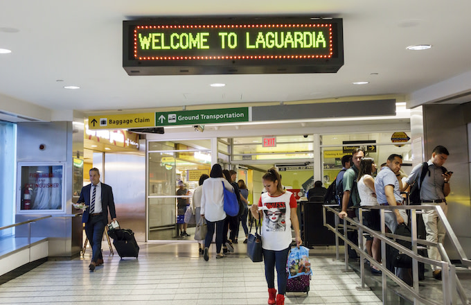 A man and woman with rolling luggage inside the LaGuardia Airport.
