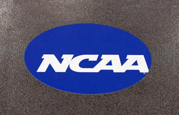 NCAA logo is displayed on the floor during the NCAA Men's Gymnastics Championship.