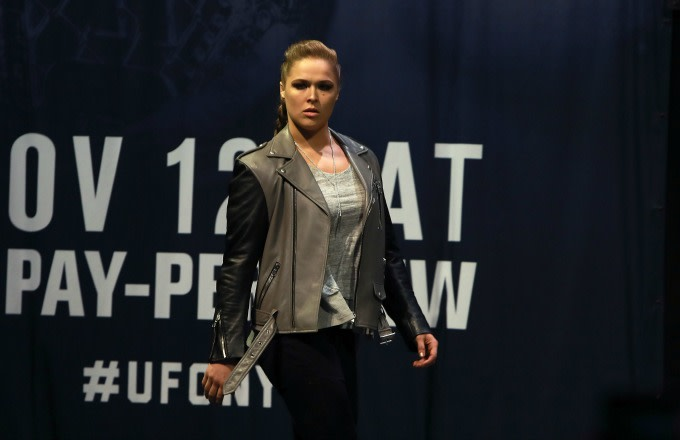 Ronda Rousey walks across the stage at a UFC 205 press conference.