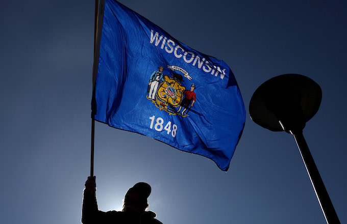 A demonstrator waves a Wisconsin flag in front of the Wisconsin State Capitol.