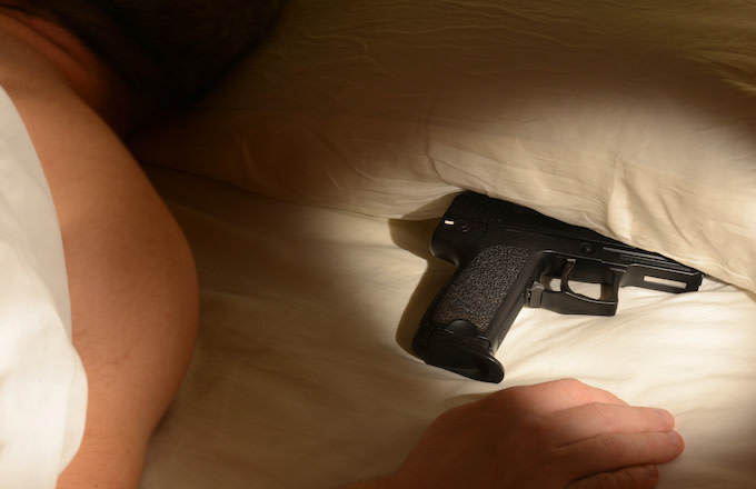 Man in bed with gun underneath pillow.