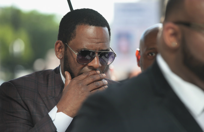 R&B singer R. Kelly covers his mouth as he speaks