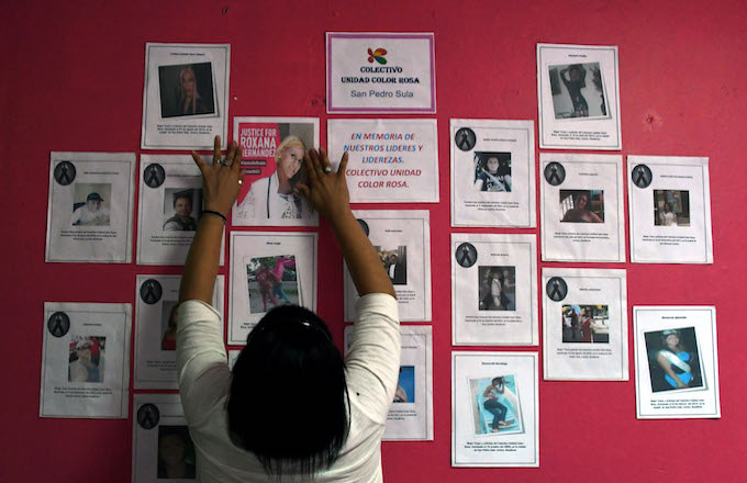 A member of the Pink Unity Collective places a poster on a board, demanding justice.