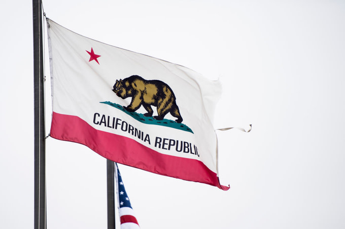 The state flag of California flies near the Los Angeles International Airport