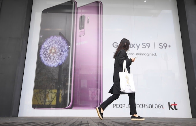 A woman walks past an advertisement for the Samsung Galaxy S9.