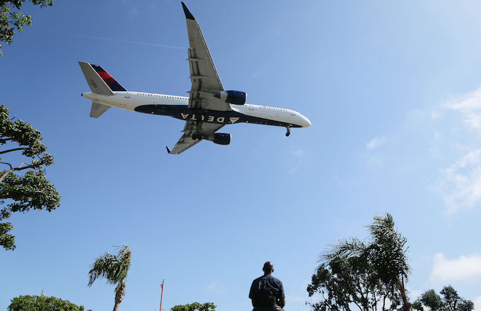 Man watches as a Delta Air Lines plane lands at Los Angeles International Airport.