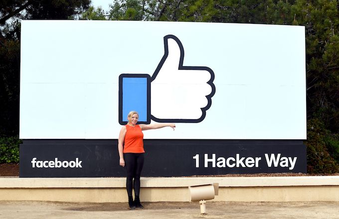 Woman making thumbs down sign outside Facebook headquarters.