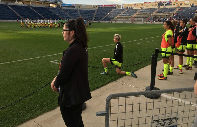 Megan Rapinoe kneels during the national anthem before an NWSL game.