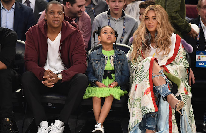 This is Jay Z, Beyoncé, and Blue Ivy at a basketball game.