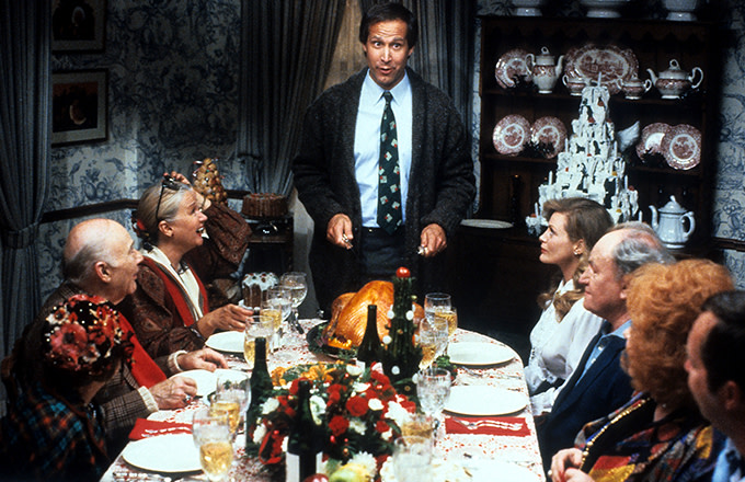 Chevy Chase stands at the head of the table in a scene from the film 'Christmas Vacation', 1989.