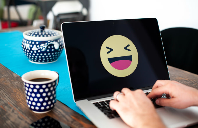 A laptop with a happy emoji face displayed