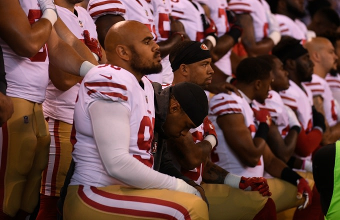 49ers players take a knee.