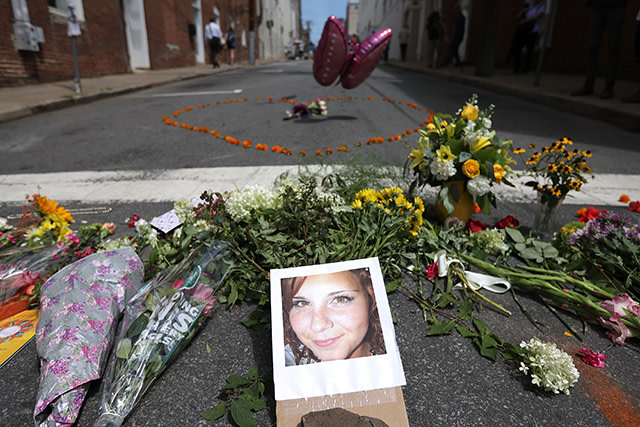 Flowers surround a photo of 32-year-old Heather Heyer