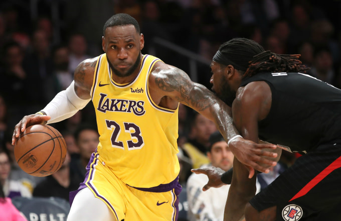 LeBron James #23 of the Los Angeles Lakers dribbles past Montrezl Harrell