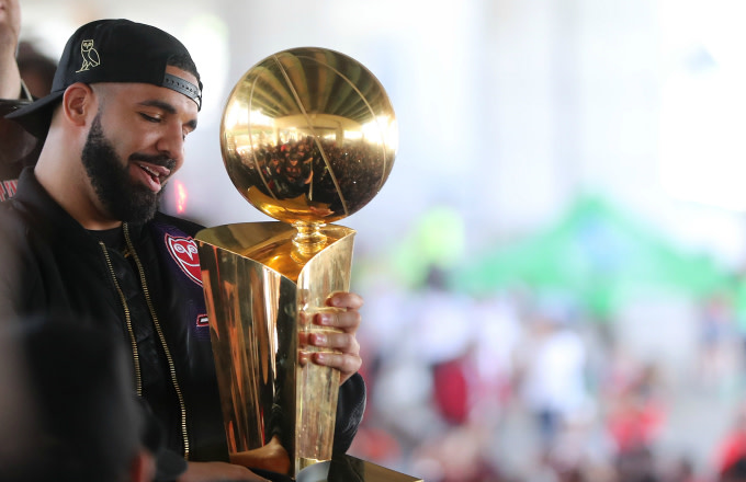 Drake holds the Larry O'Brien NBA Championship Trophy