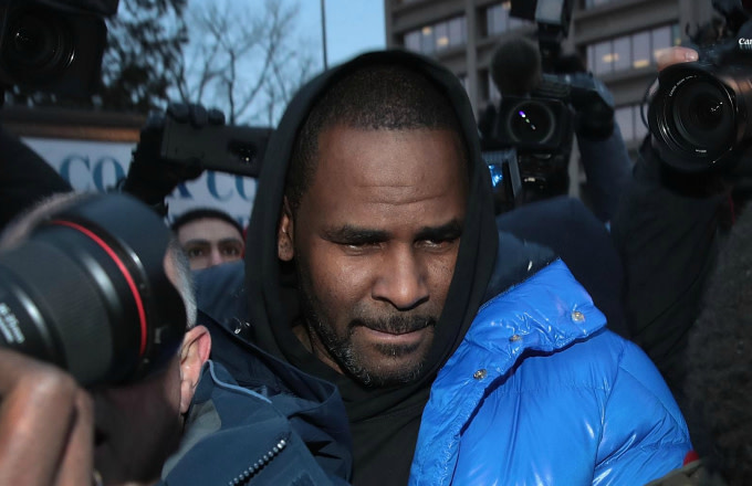 R. Kelly fights his way through photographers