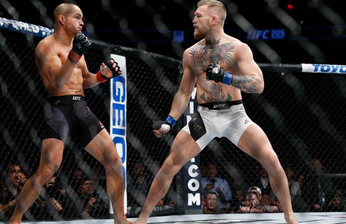 Conor McGregor (blue gloves) fights Eddie Alvarez (red gloves) in their lightweight title bout.