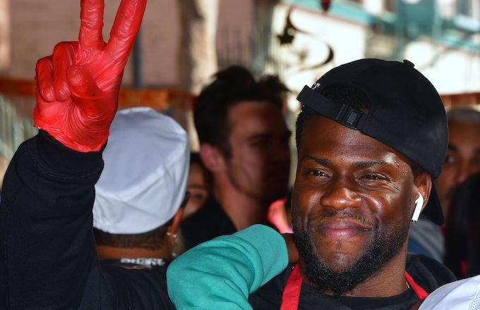 Kevin Hart gestures between serving volunteers who will serve the homeless.