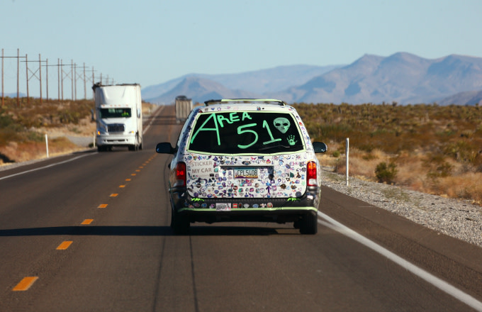A car drives with 'Area 51' written on the back
