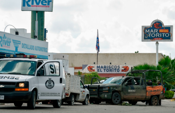 A forensic service van is seen next to a vehicle with bullet holes