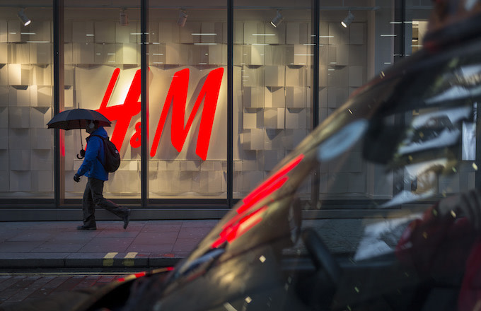 A pedestrian under an umbrella walks past the H&M logo.
