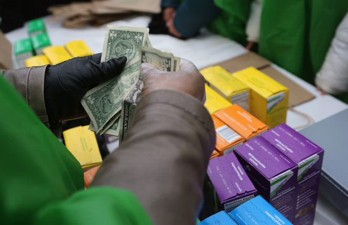 Money is collected as Girl Scouts sell cookies.