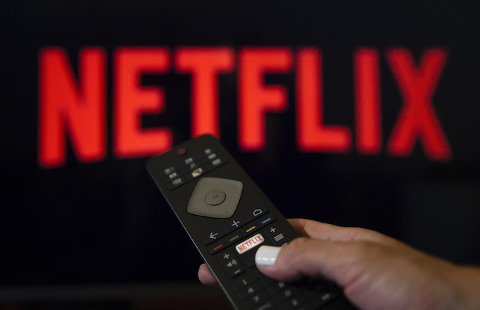 A person holds a Netflix remote control.